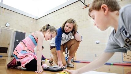 Woodson Kindergarten Center Principal Jessica Cabeen helps Woodson Coding Club members Jada Swift and Calvin Bambrick Tuesday. Eric Johnson/photdoesk@austindailyherald.com
